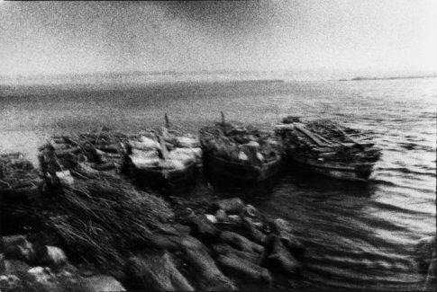 Barques pleines de bois au pied du champ de crémation.