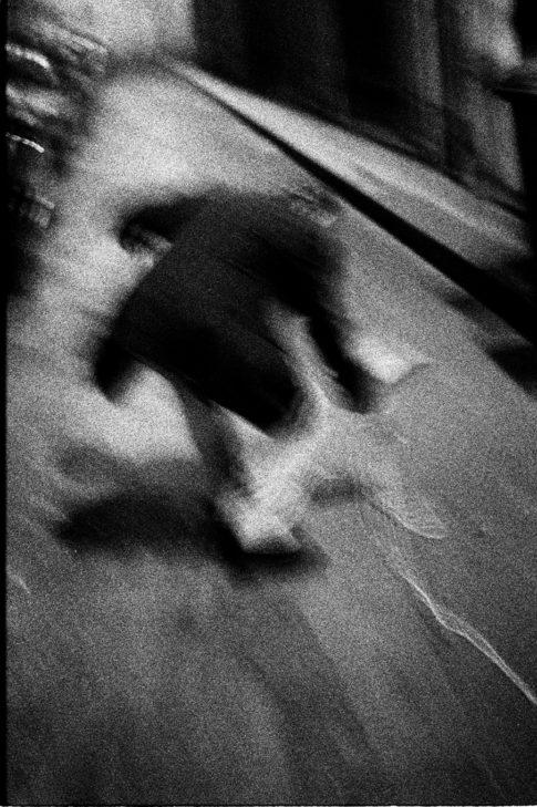 Homme seul qui se baisse dans une rue de Paris.