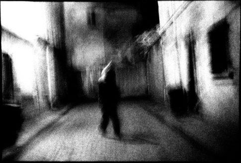 Ombre humaine dans une rue parisienne la nuit.